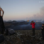 friends photograhing each other in front of volcano