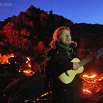 playing guitar in front of volcano